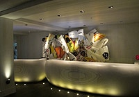 The lobby of The Waikiki EDITION features an artsy patchwork collage made of broken surfboards once used by pro surfers