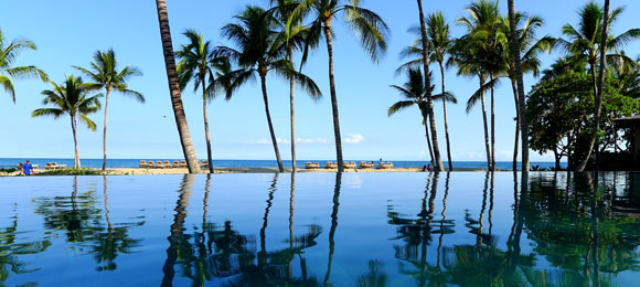 The adult-only, infinity-edge Palm Grove Pool at Four Seasons Hualalai at Historic Ka'upulehu