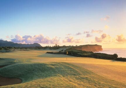 The fairway on the 16th hole at Poipu Bay Golf Course at sunrise, one of GAYOT's Top 10 Golf Courses in Hawaii