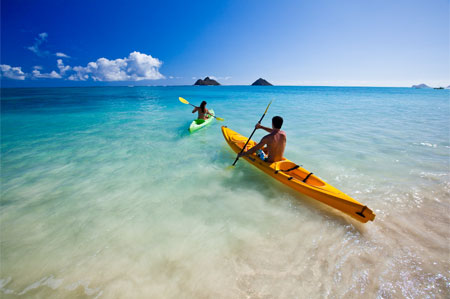 A couple pulls kayaks through the surf at Kailua on Oahu, one of GAYOT's Top 10 Hawaii Beaches