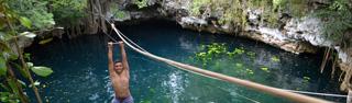 Zip-lining across a cenote near Puerto Morelos in Mexico