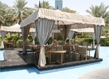 Dine in a unique setting surrounded by palm trees and a pool at Eauzone at the One&Only Royal Mirage
