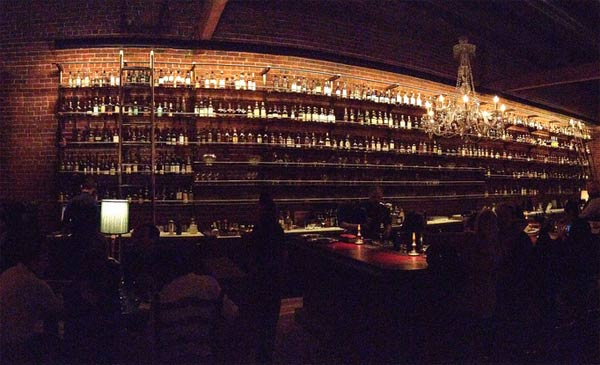 A dark, cozy bar with liquor shelves full of all the bourbon one could need