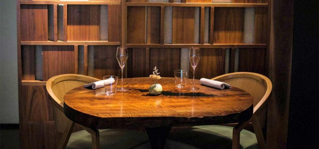 A handmade walnut table in the intimate dining room of chef Dominique Crenn's Atelier Crenn