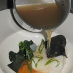 Citrus dashi broth being poured on the cod