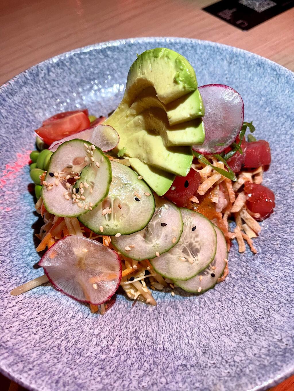 Tuna poke bowl, sashimi grade ahi tuna poke, crispy wontons, green papaya slaw, miso dressing, brown rice